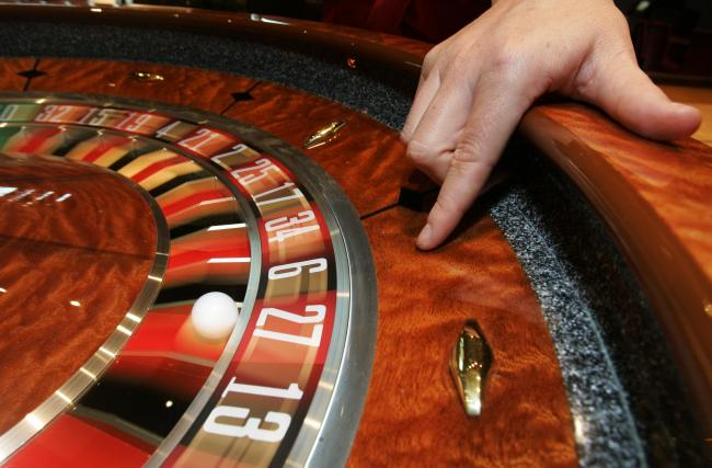 File photo dated 5/2/2008 of a croupier with a roulette table. Five of the UK's biggest gambling companies have committed to a series of measures to address problem gambling, including a major increase in funding for addiction, following government cr