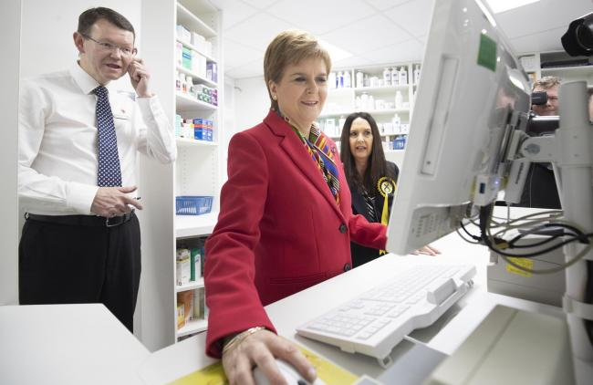 SNP leader Nicola Sturgeon with pharmacist Alasdair Macintyre (left)
