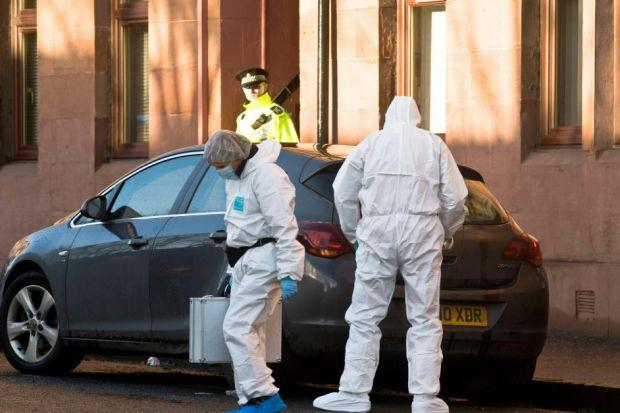 Police forensics officers examine a car near the Petershill Road murder scene