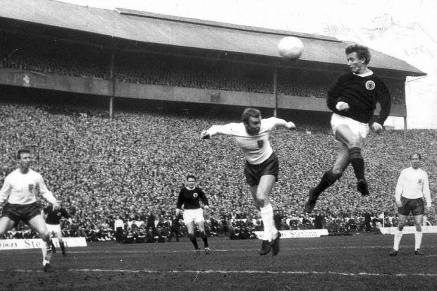 Denis Law outjumps Bobby Moore to score with a header for Scotland during their 4-3 defeat against  England at Hampden in 1966