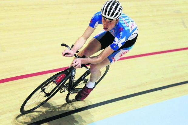 A member of the Scottish cycling team takes to the track