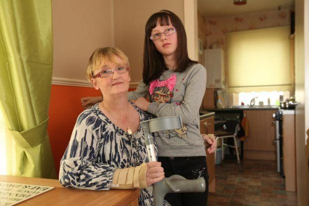 Ellie McBride, 10, cares for her mother Marion, who has severe arthritis and had one leg amputated below the knee