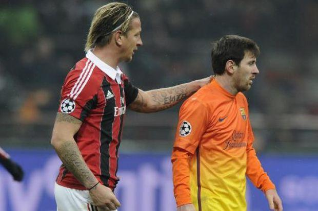 Lionel Messi is consoled by Milan's Philippe Mexes
