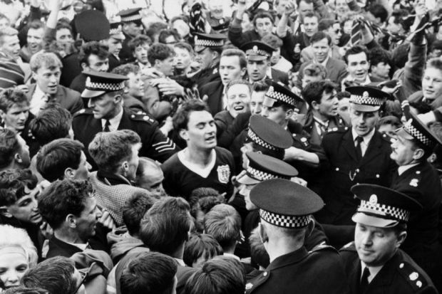Alan Gilzean, centre, is escorted off the pitch by policemen as jubilant Dundee fans invade the pitch after seeing their team beat St Johnstone 3-0 to secure the League Championship