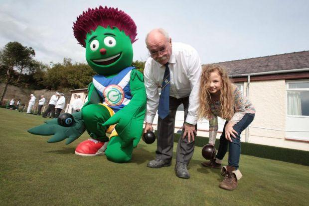Commonwealth Games Mascot Clyde joins Kate Sloan, 8, and her grandad Bob Sloan at the official opening of the greens at Jordanhill Bowling Club