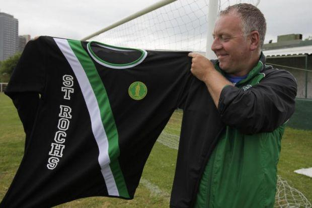 St Rock's club treasurer Frank Brady proudly holds up the team's new strip to commemorate James McGrory at the club. Picture: Mark Gibson