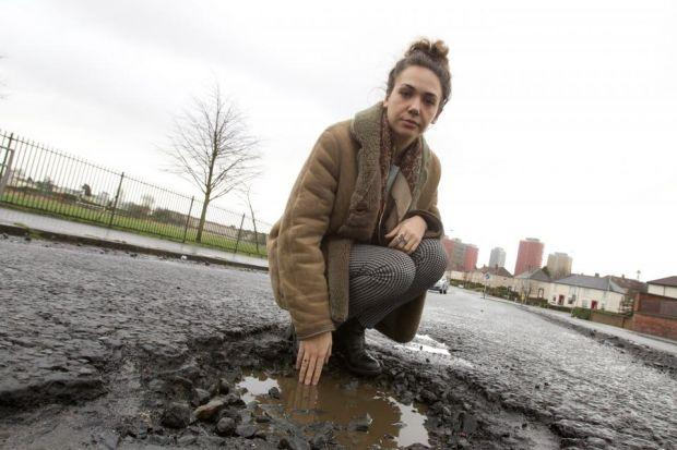 Reporter Megan at the huge pothole in Broomfield Road, Balornock, which has already cost one driver £300 to repair his car