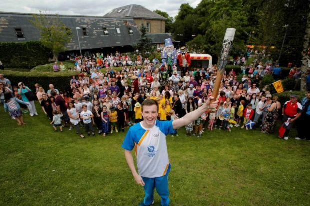 Baton bearer Ian Rae with the crowds at the East Kilbride Arts Centre. Picture: Martin Shields