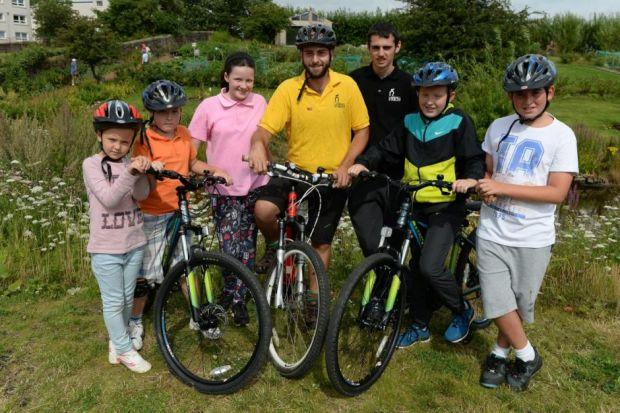Claudio Pia, centre, takes local schoolchildren Amy Dragsnes, Cameron Dragsnes, Bethany Kane, Gary Pendres, Dillon O'Donnell, and Jack Boyle out for a cycle, and, left, also gives classes on bike repair. Pictures: Nick Ponty