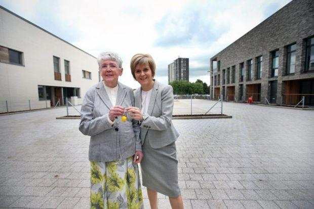 Annie O'Donnell and Nicola Sturgeon toast Annie's move from Norfolk Court, behind, to new home