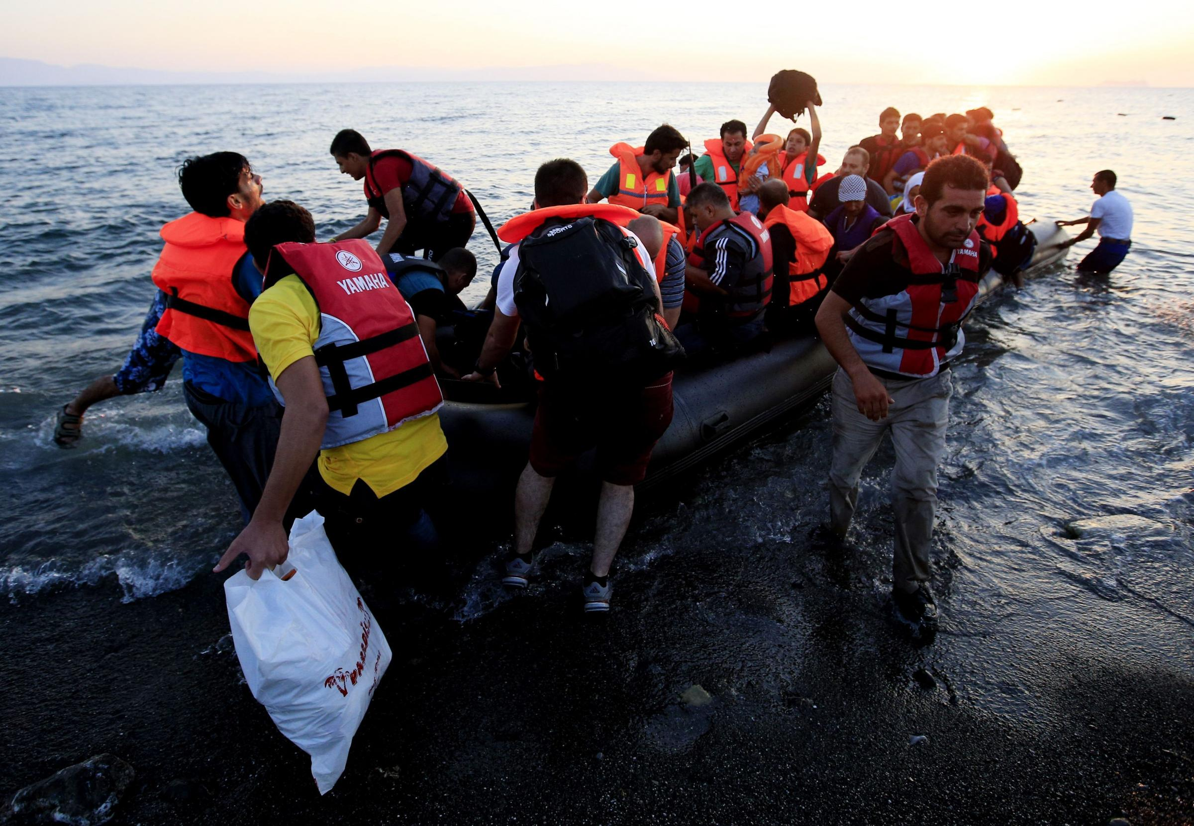 Migrants and refugees in a rubber dinghy arrive on the beach at Psalidi near Kos Town, Kos, Greece. PRESS ASSOCIATION Photo. Picture date: Friday August 21, 2015. See PA story POLITICS Kos. Photo credit should read: Jonathan Brady/PA Wire. (37486776)