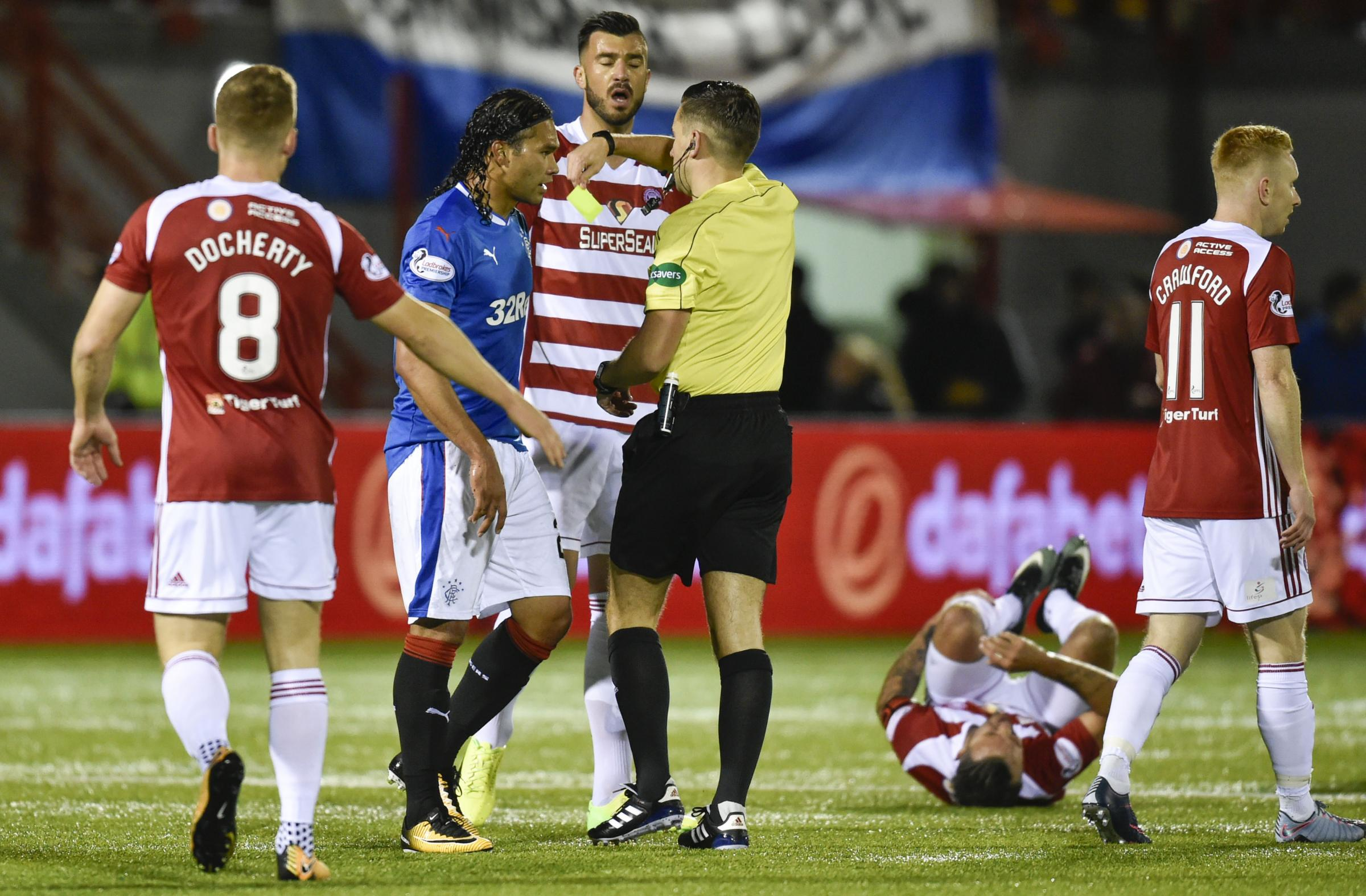 Carlos Pena is shown a yellow card after a challenge on Dougie Imrie