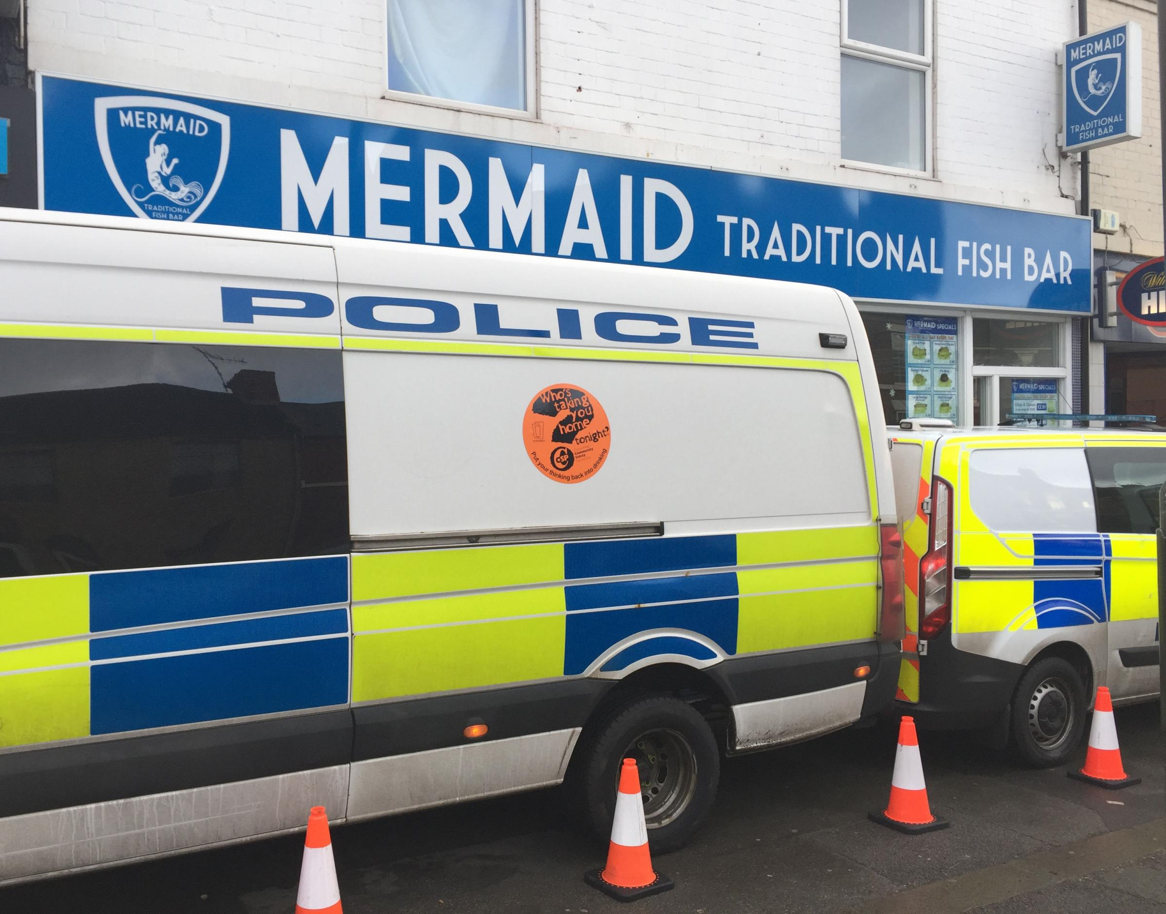 Police vans parked up outside a fish and chip shop in Chesterfield
