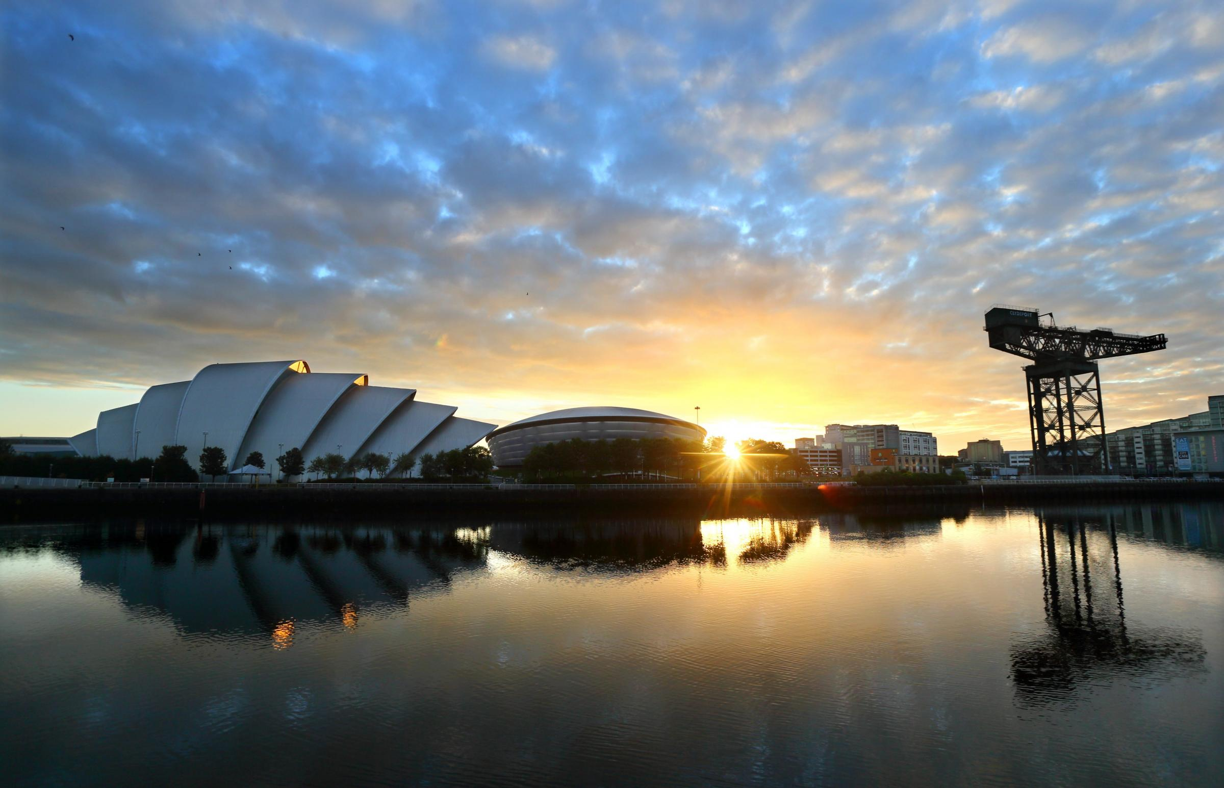 The sun rises behind the Clyde Auditorium, SSE Hydro and Finnieston crane with all reflected in the River Clyde. Photograph taken at 05.05am on Monday 30 June 2014.....  Photograph by Colin Mearns..30 June 2014.