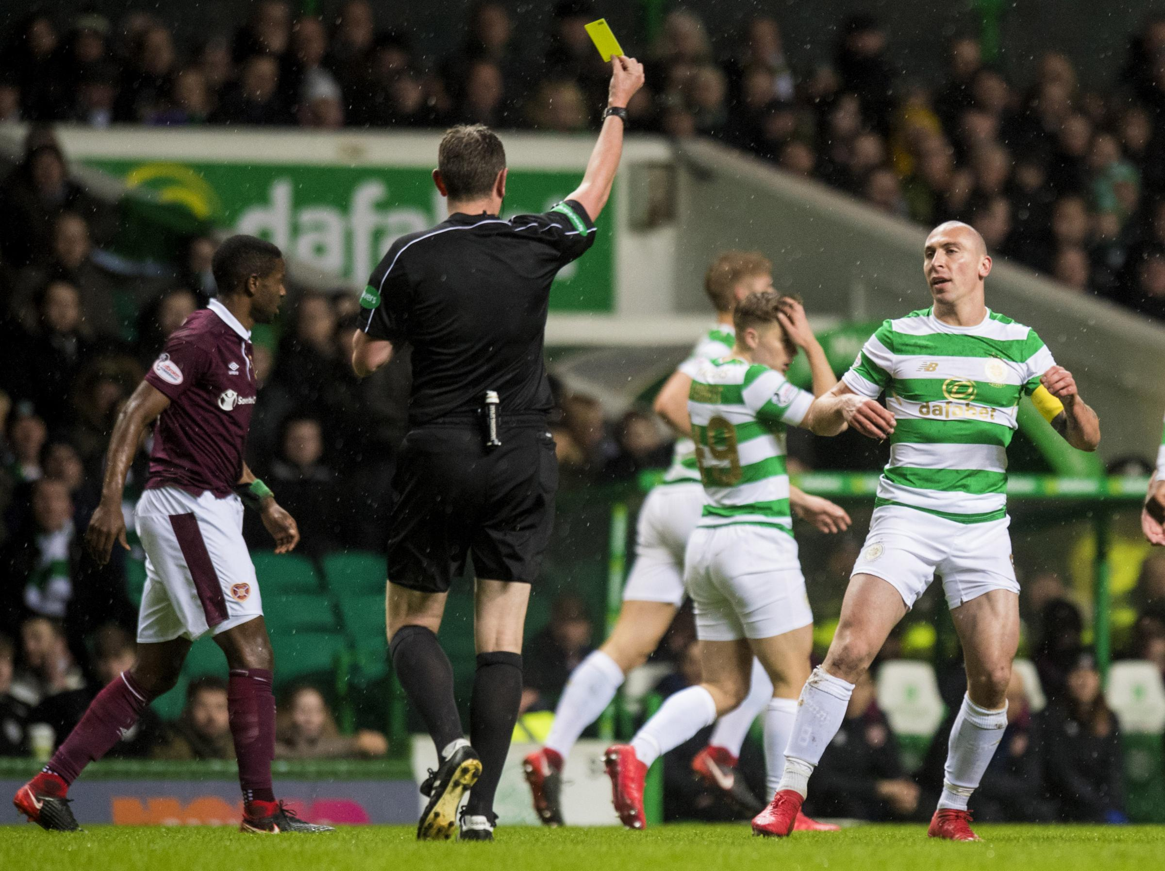 Scott Brown is booked by referee Craig Thomson