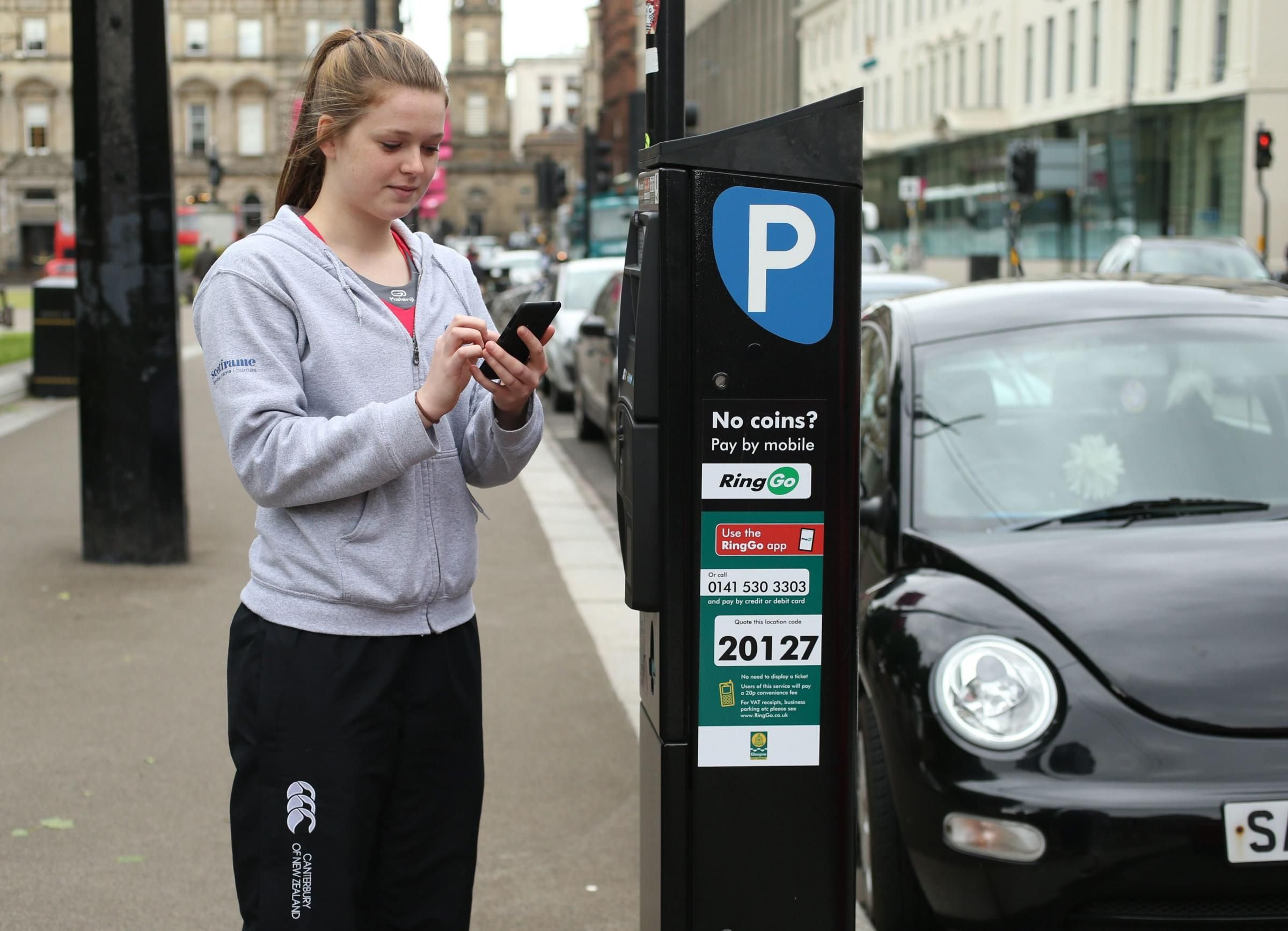 Launch of Ring Go cashless parking in Glasgow. Pictured is Jenny Hudson age 19 from Glasgow using the Ring Go app on a phone to pay for parking at one of the parking meters in George square...   Photograph by Colin Mearns.2 June 2015.