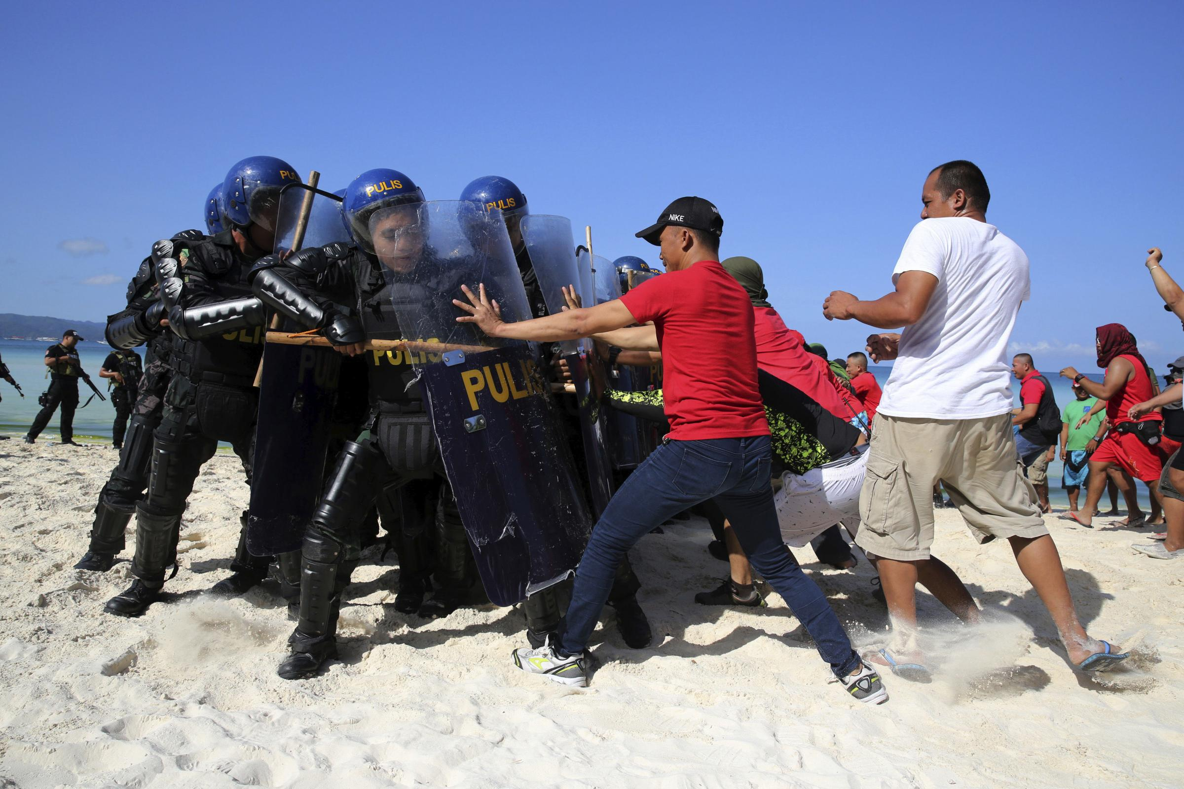 Philippines policemen acting as protesters attack anti-riot police during a security drill at the country's most famous beach resort island of Boracay, in central Aklan province, Philippines Wednesday, April 25, 2018
