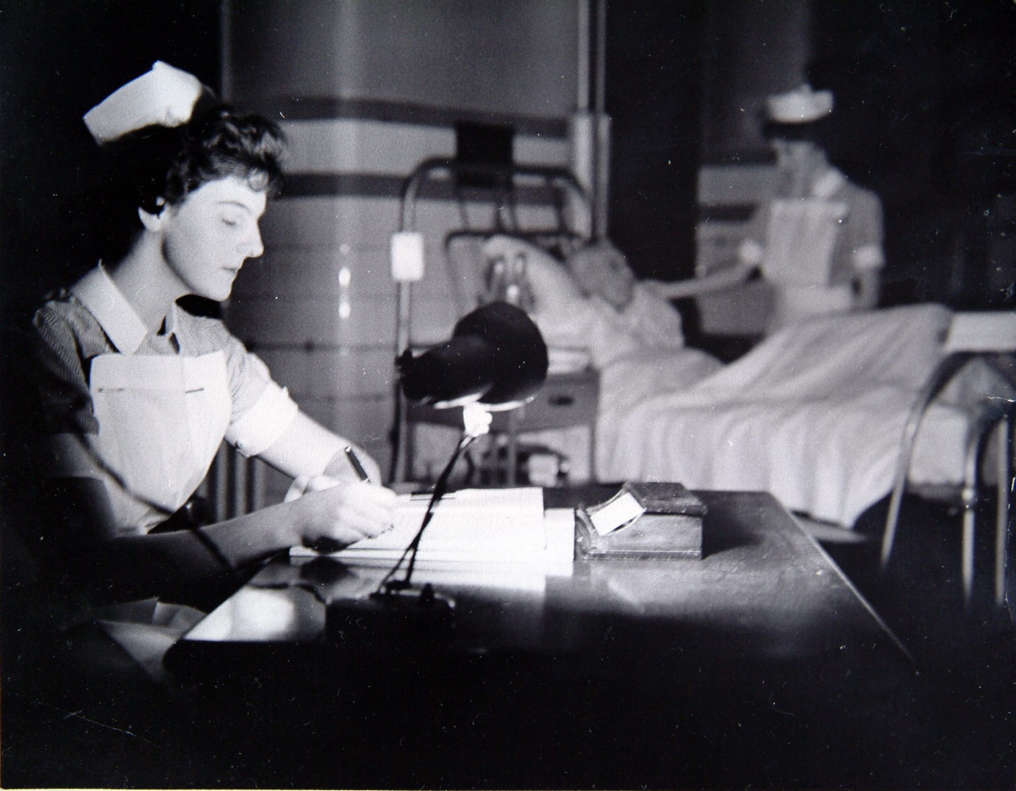 Glasgow Royal Infirmary. The ward lights are dimmed and the curtains drawn when the night duty nurses take over at 9pm. A young nurse sits at her desk checking over the day reports of the patients. In the background her colleague adjusts the pillows