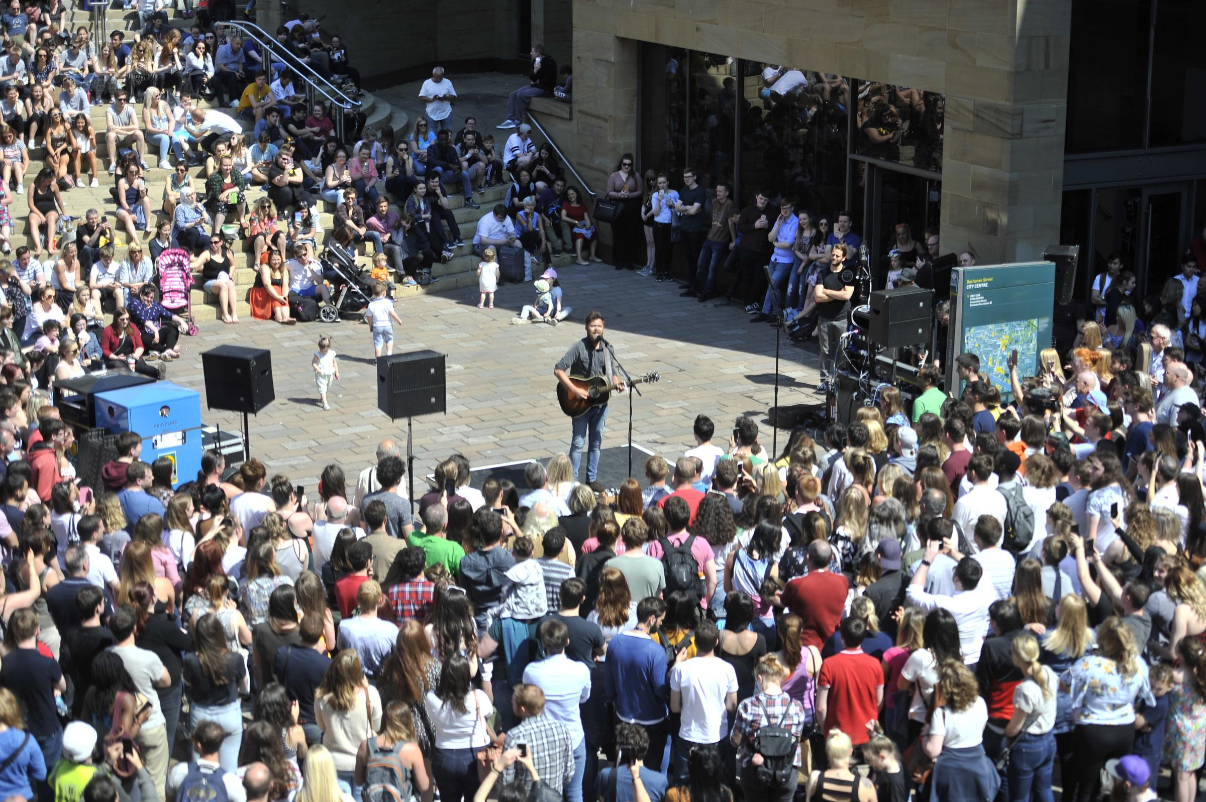 GLASGOW, SCOTLAND - MAY 25: crowds watch Mike Rosenberg from band Passenger performs to the public on Buchanan street May 25, 2018 in Glasgow, Scotland. (Photo by Jamie Simpson/Herald & Times) - JS.