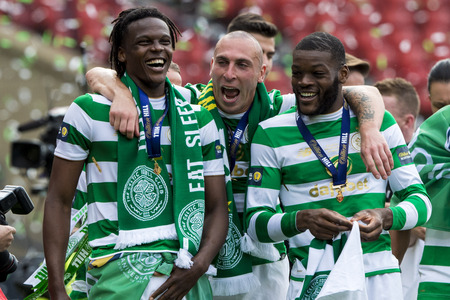 Dedryck Boyata celebrates with Scott Brown and Oliver Ntcham and is hoping for more success at the World Cup