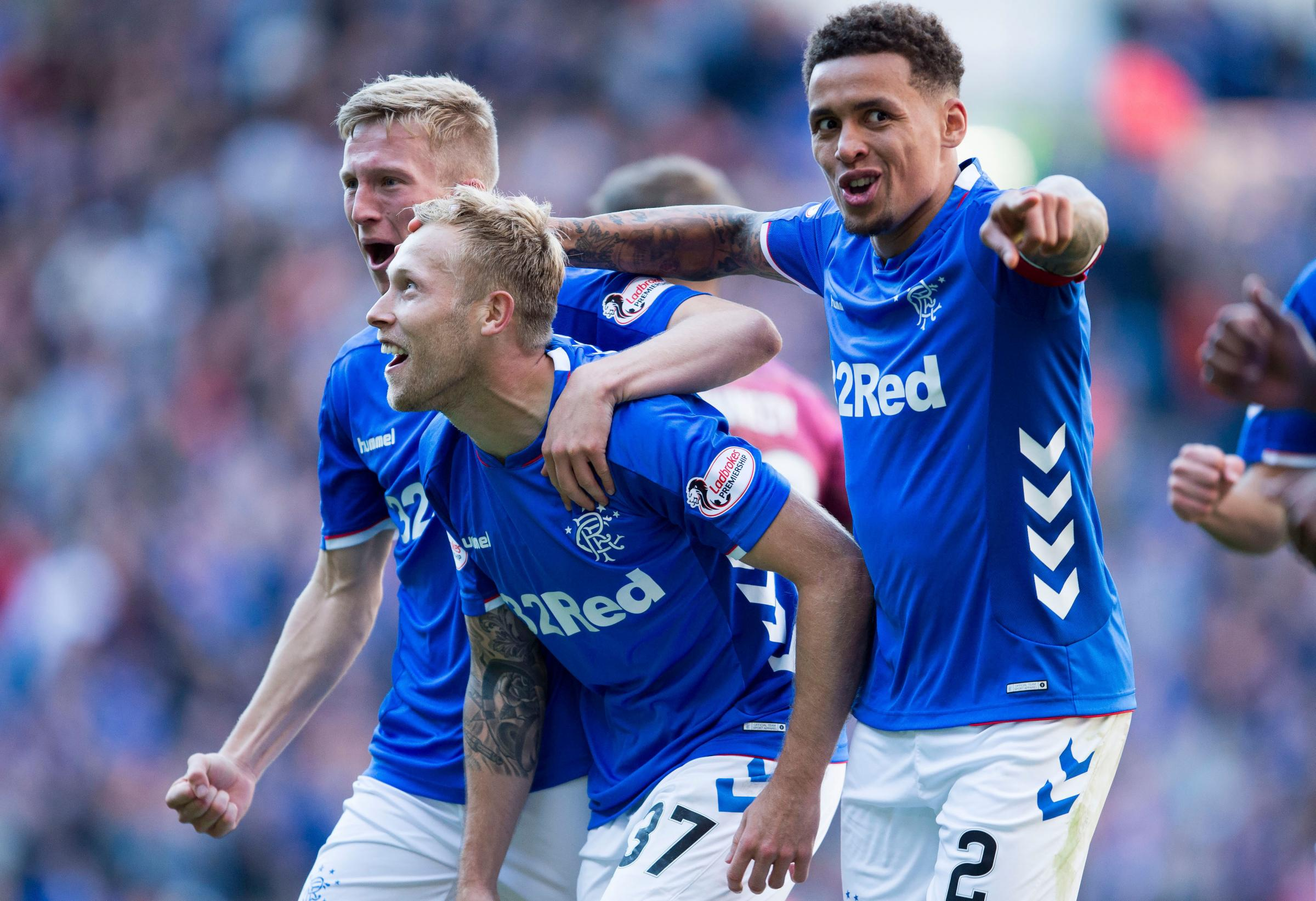 Scott Arfield celebrates with Ross McCrorie and James Tavernier