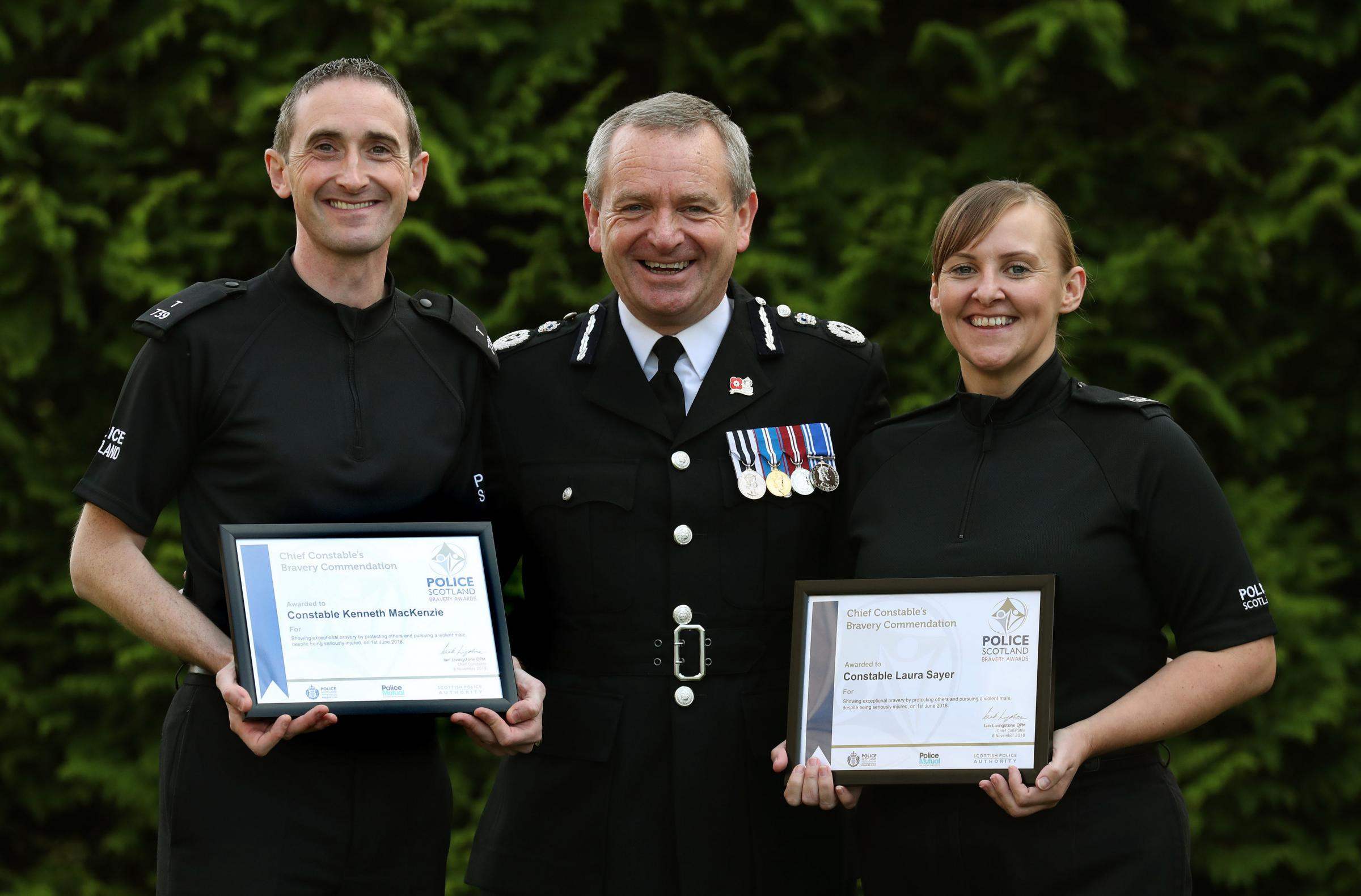 Police Constables Laura Sayer and Kenneth MacKenzie who were seriously injured during an incident in Greenock have received an award for bravery from Chief Constable Iain Livingstone(C) , at the Scottish Police College, Tulliallan, Kincardine. PRESS ASSOC