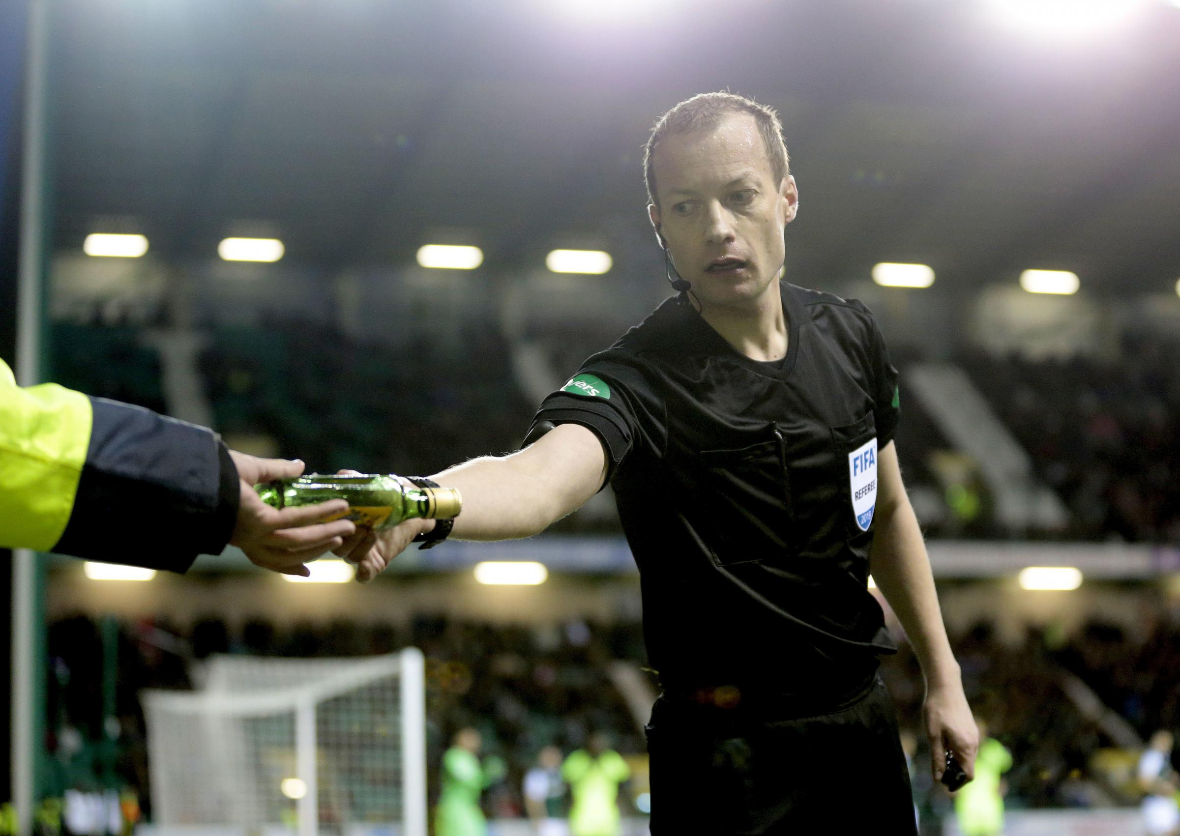 Referee Willie Collum removes a bottle from pitch during Hibernian's meeting with Celtic in the William Hill Scottish Cup quarter-final match at Easter Road on Saturday. Picture: Graham Stuart/PA Wire.