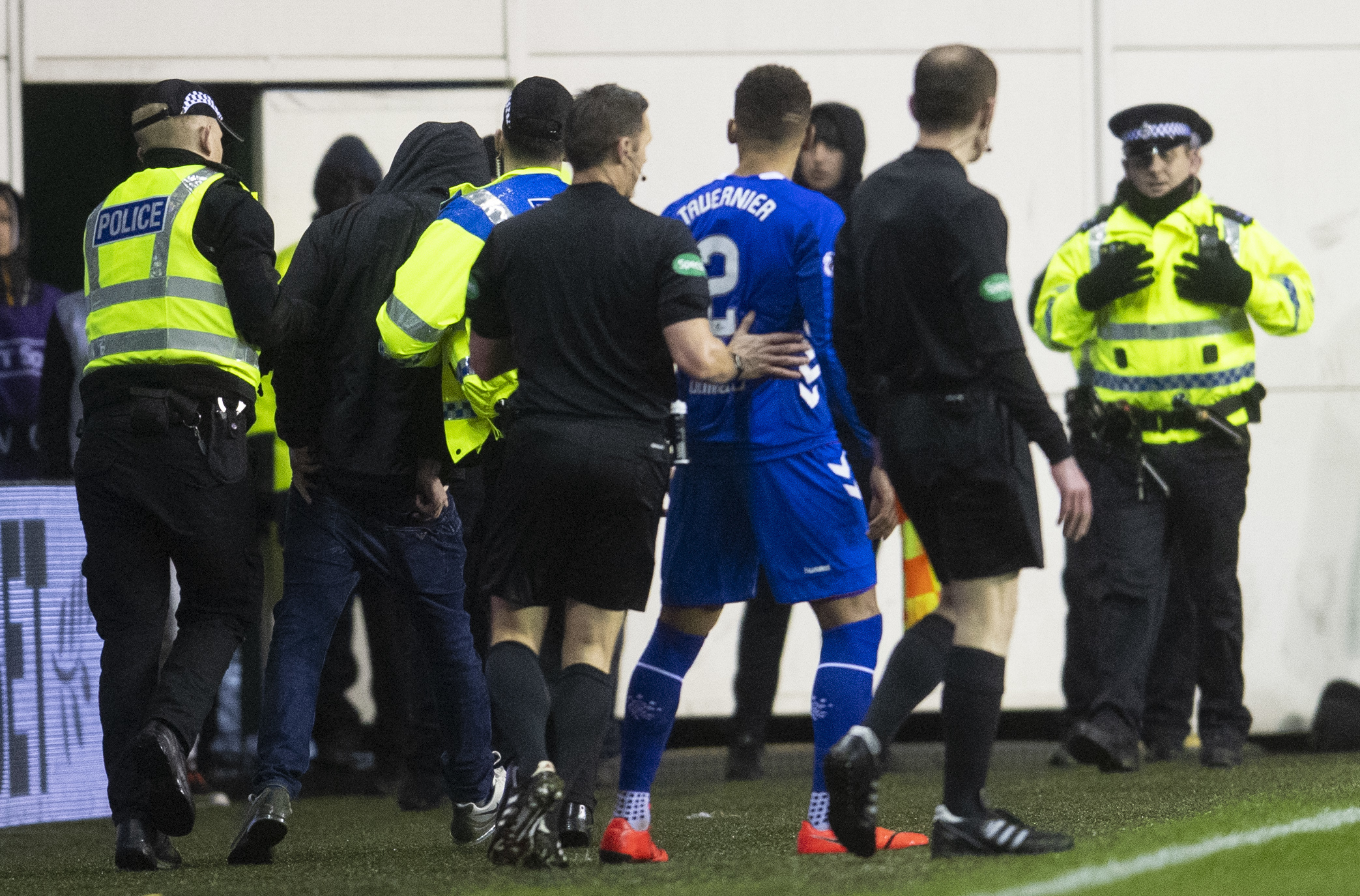 A fan is lead away by the police after an altercation with Rangers captain James Tavernier