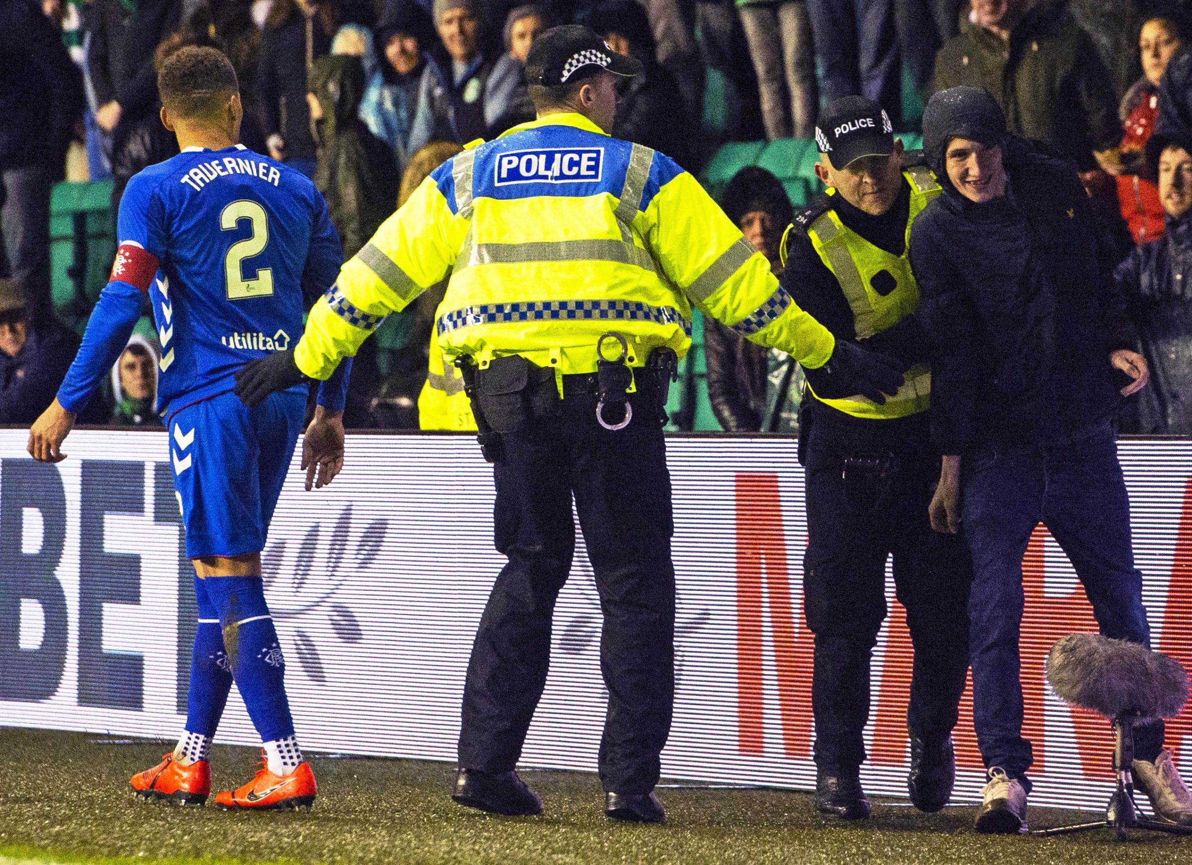 A Hibs fan is led away from police on Friday night after running onto the park to confront Rangers captain James Tavernier.