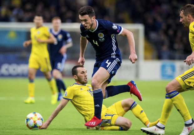 Evening Times: Scotland's John McGinn (centre) skips away from Kazakhstan's Gafurzhan Suyumbayev