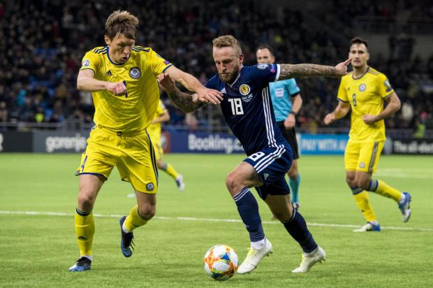 Evening Times: Scotland's Johnny Russell (right) competes with Kazakhstan's Yan Vorogovskiy