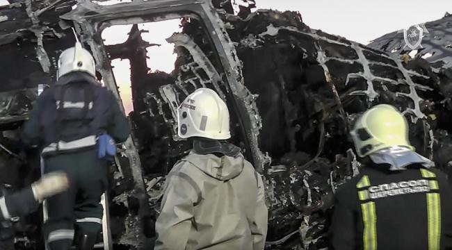 This image taken from a video distributed by Russian Investigative Committee on Monday, May 6, 2019, shows employees of the Russian Emergency Situations work at the wreckage of Sukhoi SSJ100 aircraft of Aeroflot Airlines in Sheremetyevo airport, outside M