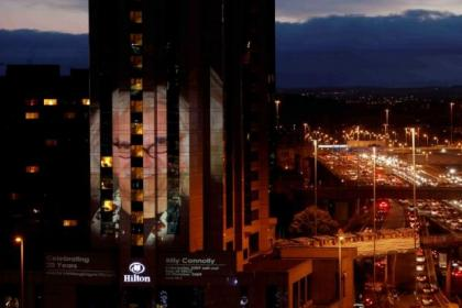 The huge picture of Billy Connolly is projected onto the side of the Hilton building