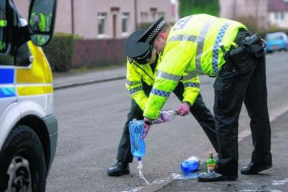 Down the drain: police dispose of confiscated alcohol taken off street drinkers