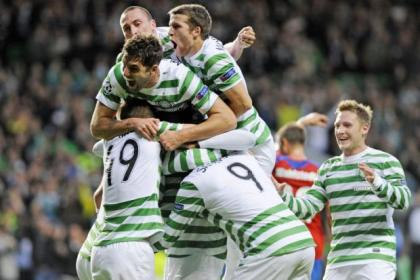 Victor Wanyama is swamped by team-mates after his header ensured there was no way back for Helsingborgs and sealed Celtic's place in today's Champions League group stage draw