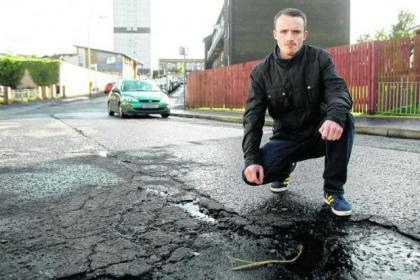 David Martin beside some of the potholes he is complaining about