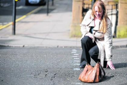 Reporter Fiona McKay avoids the traffic to show the depth of the pothole in Hope Street