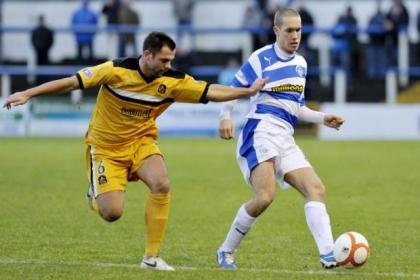 Morton's Michael Tidser gets his jersey tugged by Dumbarton's Chris Turner.