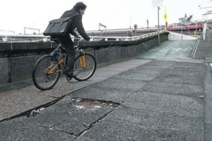 Cyclists are forced to negotiate uneven paving and flooded potholes