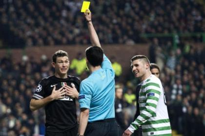 Referee Alberto Mallenco issues a yellow card to Juve's Stephan Lichtsteiner and Celtic's Gary Hooper
