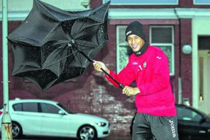 Off his brolly...new Thistle signing Lyle Taylor gets his own introduction to the Glasgow weather Picture: Colin Templeton