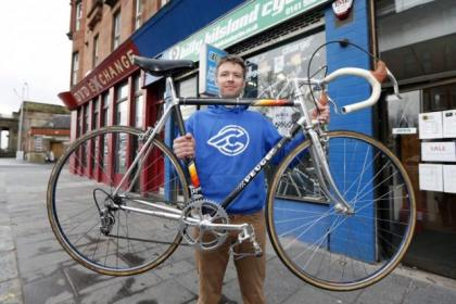Shop manager Mark Allan with the bike and polka dot jersey, right Pictures: Colin Templeton