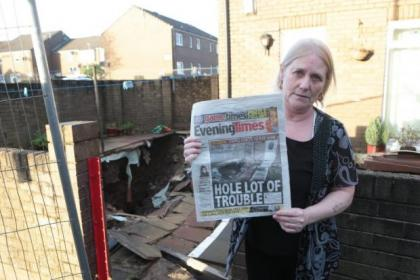 Millroad Drive resident Isabel Weir outside the collapsing property with a copy of our front page story about the ongoing subsidence