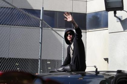 Justin Bieber, who was detained in Florida, waves as he leaves the Turner Guilford Knight Correctional Center in Miami. The teenager was released from jail after his arrest on charges of driving under the influence and drag racing. He also faces a petition to have him expelled from the US