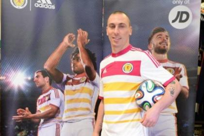 Scott Brown shows off the bright new Scotland away kit, which pays tribute to the old Lord Rosebery colours of white, pink  and yellow