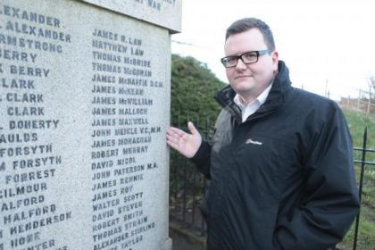 Councillor David McDonald points out John Meikle's name on the war memorial