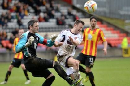 Partick Thistle goalkeeper Paul Gallacher beats Hearts' Dale Carrick to the ball and clears away the danger