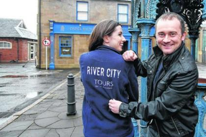 Karen Bradley, one of the most experienced River City tour guides, in the Main Street with Stephen Purdon who plays Shellsuit Bob