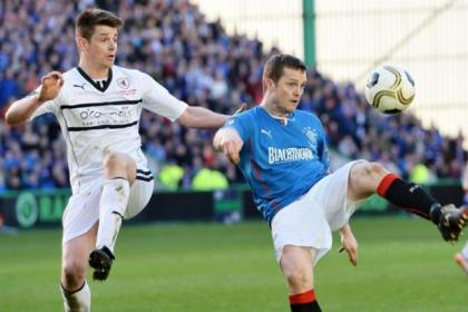 Raith Rovers' Dougie Hill pays close attention to Rangers' Jon Daly