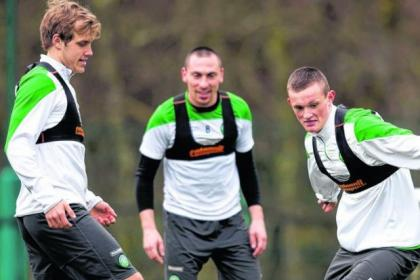 Celtic's starlet Liam Henderson skips past Teemu Pukki at training in Lennoxtown as Scott Brown looks on in approval